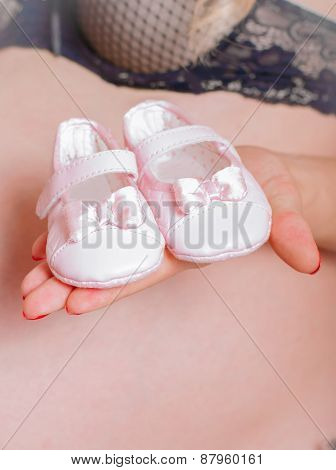 Baby socks in  hands of pregnant woman