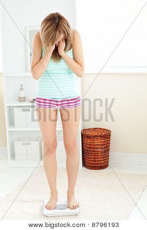 Jovem mulher caucasiana de pé sobre uma balança no banheiro