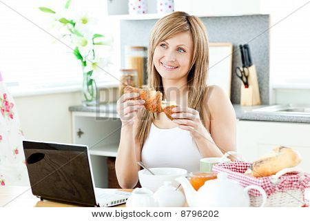 Smiling Woman Having Breakfast In Front Of The Laptop In The Kitchen