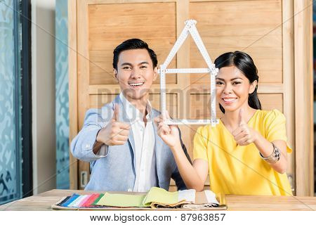 Asian couple with folding rule in furniture store