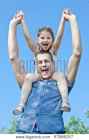 Happy little child on uncle shoulders outside in nature enjoying beautiful day