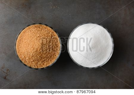 Two bowls of sugar. One bowl of granulated raw turbinado sugar and a second bowl of white granulated sugar. Horizontal format on a used baking sheet.