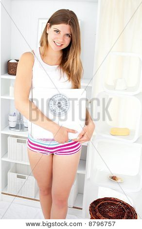 Smiling Woman Holding A Scale In The Bathroom