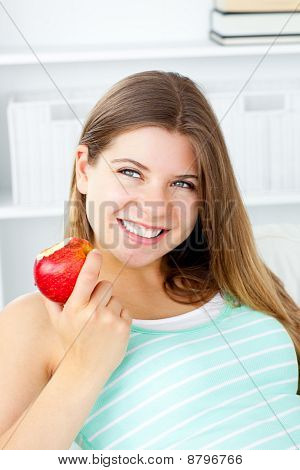 Smiling Young Woman Holding An Apple In Her Hand