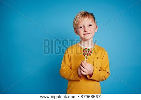 Cute lad with sweet lollipop looking at camera