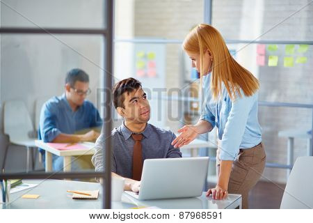 Young businesswoman consulting colleague in office