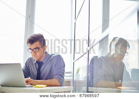 Male employee browsing in laptop