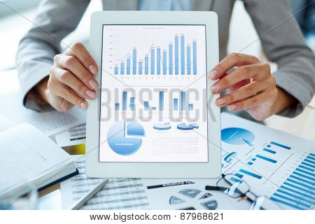 Businesswoman holding touchpad with analysis of economic situation