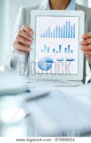 Businesswoman holding touchpad with charts and diagrams