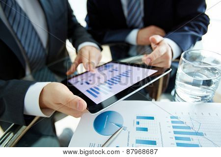 Hands of male employees discussing electronic document at workplace