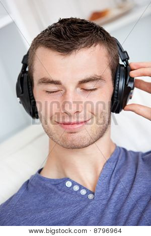 Lively Young Man Listening To Music Sitting On The Couch In The Living-room