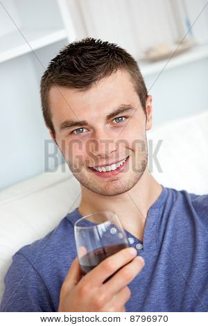 Animated Young Man Drinking Wine Looking At The Camera Sitting On The Sofa