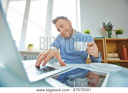 Businessman with coffee working on laptop and speaking on cellphone in office