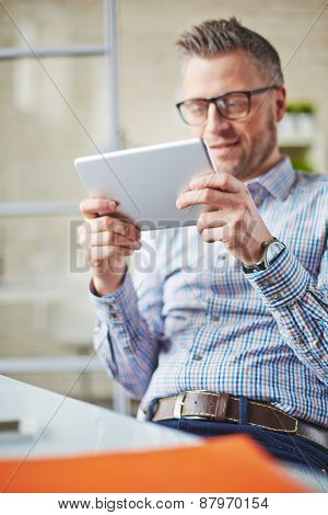 Businessman with digital tablet spending free time in office