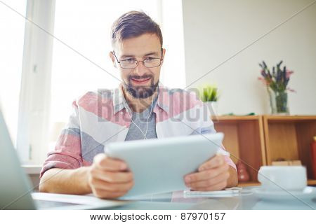 Businessman in casual using digital tablet in office