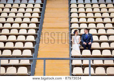 Beautiful couple sitting on football stadium stand