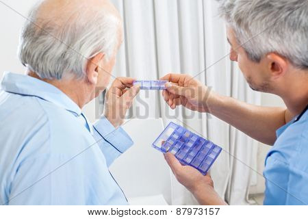 Male caretaker showing prescription medicine to senior man in bedroom at nursing home