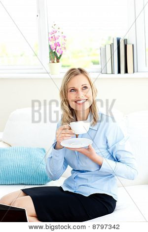 Smiling Businesswoman Holding A Cup Of Coffee Sitting On A Sofa