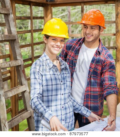 Portrait of happy female architect with male colleague in wooden cabin at site