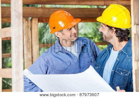 Smiling male architects discussing over blueprint in wooden cabin at site