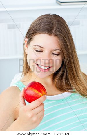 Charming Caucasian Woman Holding An Apple Sitting On A Sofa