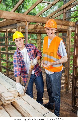 Portrait of happy male construction workers working together in timber cabin at site
