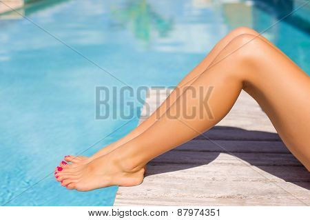 Beautiful tanned women legs by the swimming pool