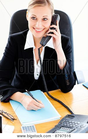 Self-assured Businesswoman Talking On Phone And Writing In Her Office