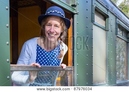 Woman in old-fashioned clothes in open window of train