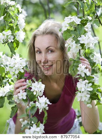 young attractive woman standing near the blossoming apple tree.
