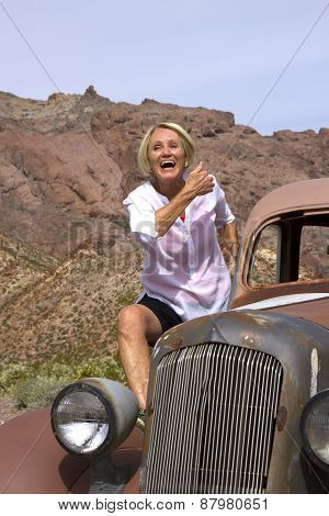Laughing Retiree Riding Antique Car In The Desert