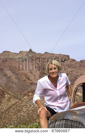 On The Go Retiree In Desert Setting On Antique Car
