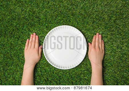 Hands lying near empty paper plate on green grass