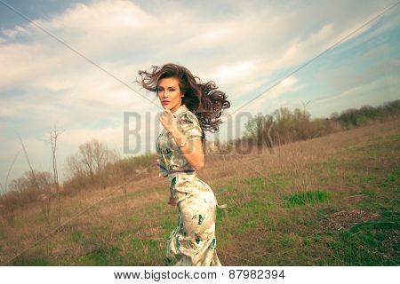 young woman in summer  dress enjoy in grass field in motion retro look and colors