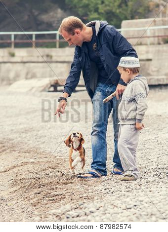 Father And Son Playing Wirh Little Puppy On The Seaside