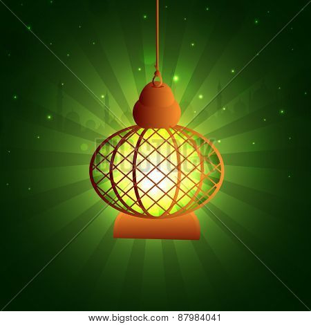 Hanging illuminated traditional lantern on green rays background for islamic holy month of prayers, Ramadan Kareem concept.