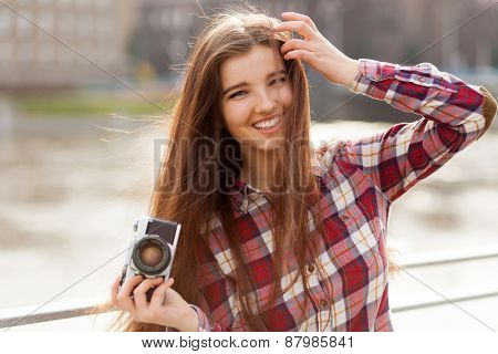 Outdoor natural portrait of a young woman with photo camera