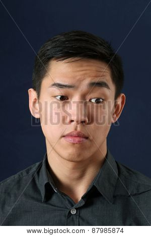Young Asian man looking sideways down