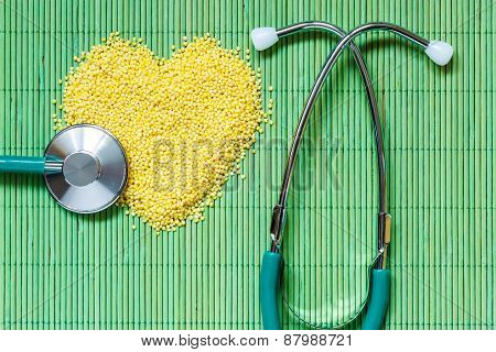 Millet Groats Heart Shaped On Green Mat Surface.