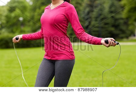fitness, sport, training, people and lifestyle concept - close up of african american woman exercising with jump-rope outdoors