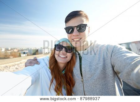 tourism, travel, people, leisure and technology concept - happy teenage couple taking selfie on city street