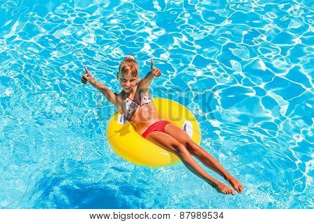 Happy child on inflatable ring in swimming pool.