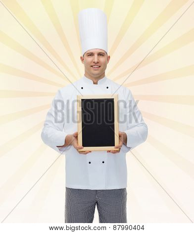 cooking, profession, advertisement and people concept - happy male chef cook showing and holding blank menu board over yellow burst rays background