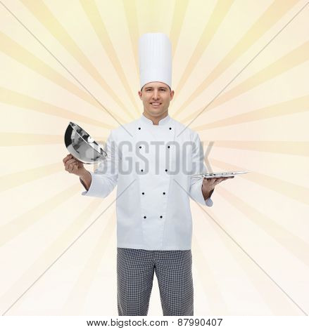 cooking, profession and people concept - happy male chef cook opening cloche cover over yellow burst rays background