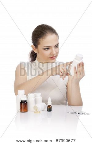 Young Woman Reading A Prescription On The Pill Bottle