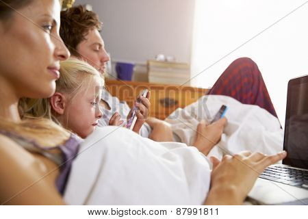 Family Lying In Bed Together Using Digital Devices