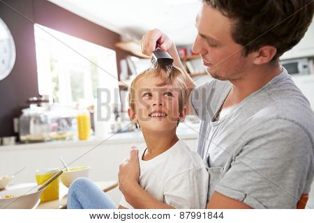 Father Brushing Son's Hair At Breakfast Table