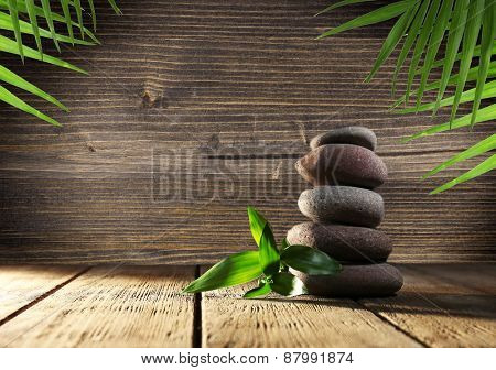 Spa stones with green leaves on wooden background