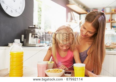 Mother And Daughter Using Mobile Phone At Breakfast Table