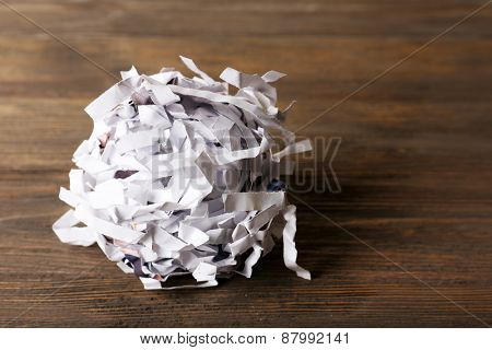 Strips of destroyed paper from shredder on wooden background